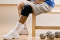 Man with knee brace gesturing the ok symbol in health club