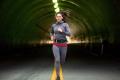 Woman jogging on run through city downtown tunnel street lights